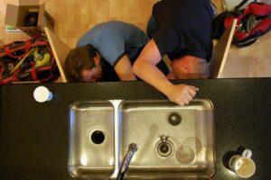 Plumbers working under sink