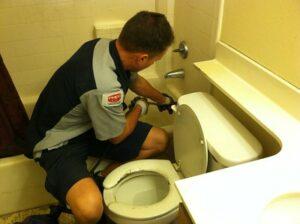 Plumber working in bathroom